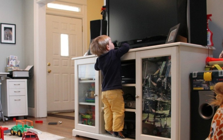 child clinging to the TV self